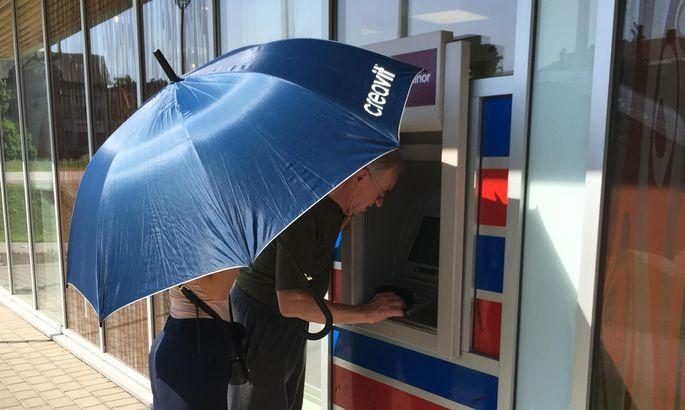 a1f0c35da68 Kolmapäeva ennelõunal oli päike niivõrd ere, et pangatöötajal tuli  vihmavarjuga automaadi kasutamiseks päikest varjata.